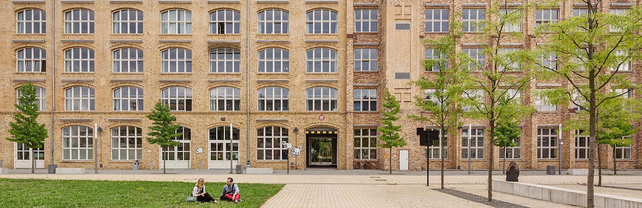 Studierende vor Gebäude C auf dem Campus Wilhelminenhof